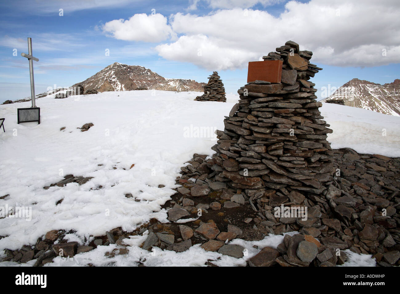 Stone cairns and resuce teams cross marker at first peak on Mount Aragats. Armenia, Southwest Asia - Stock Image