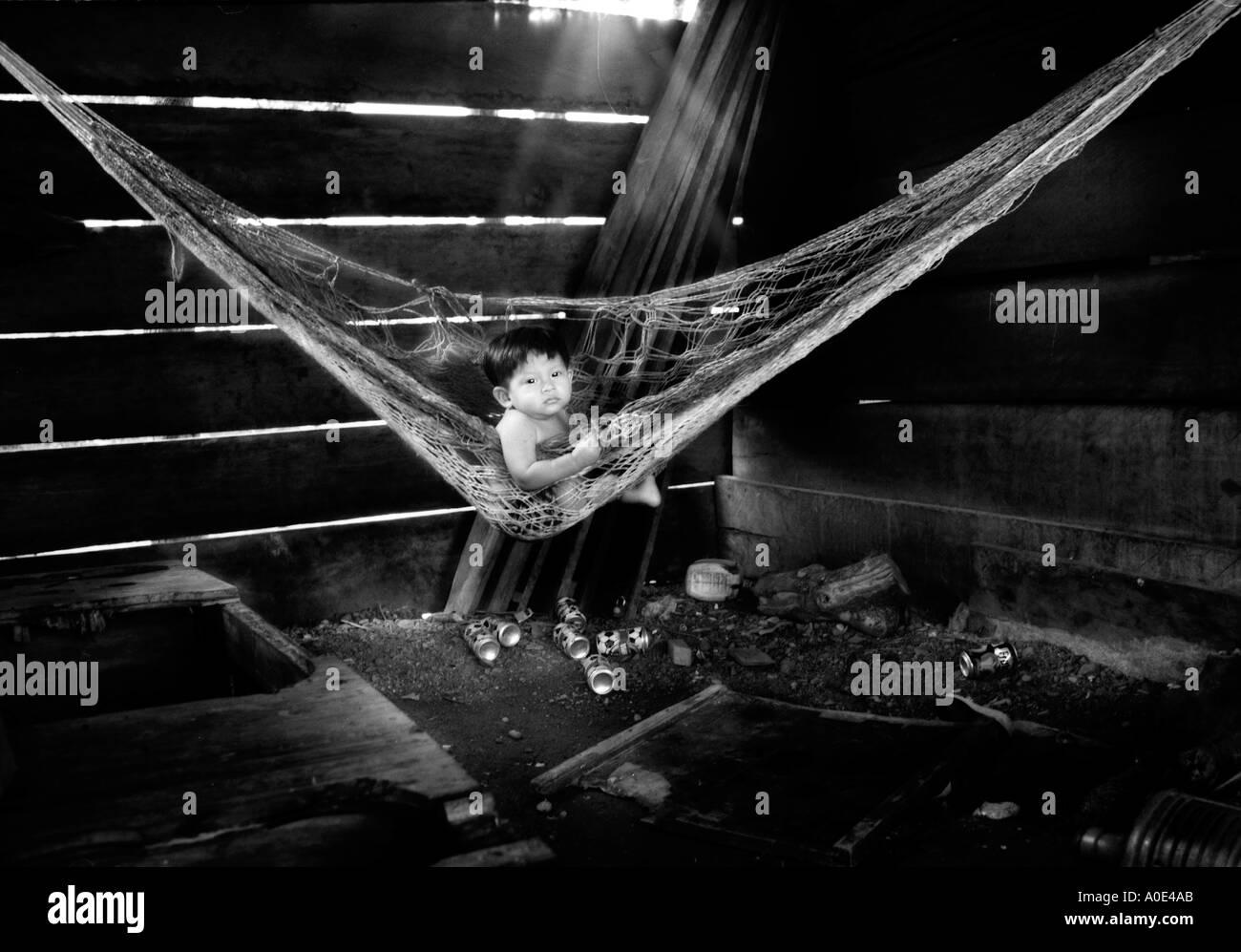 Baby alone in hammock Puerto Barrios Guatemala - Stock Image