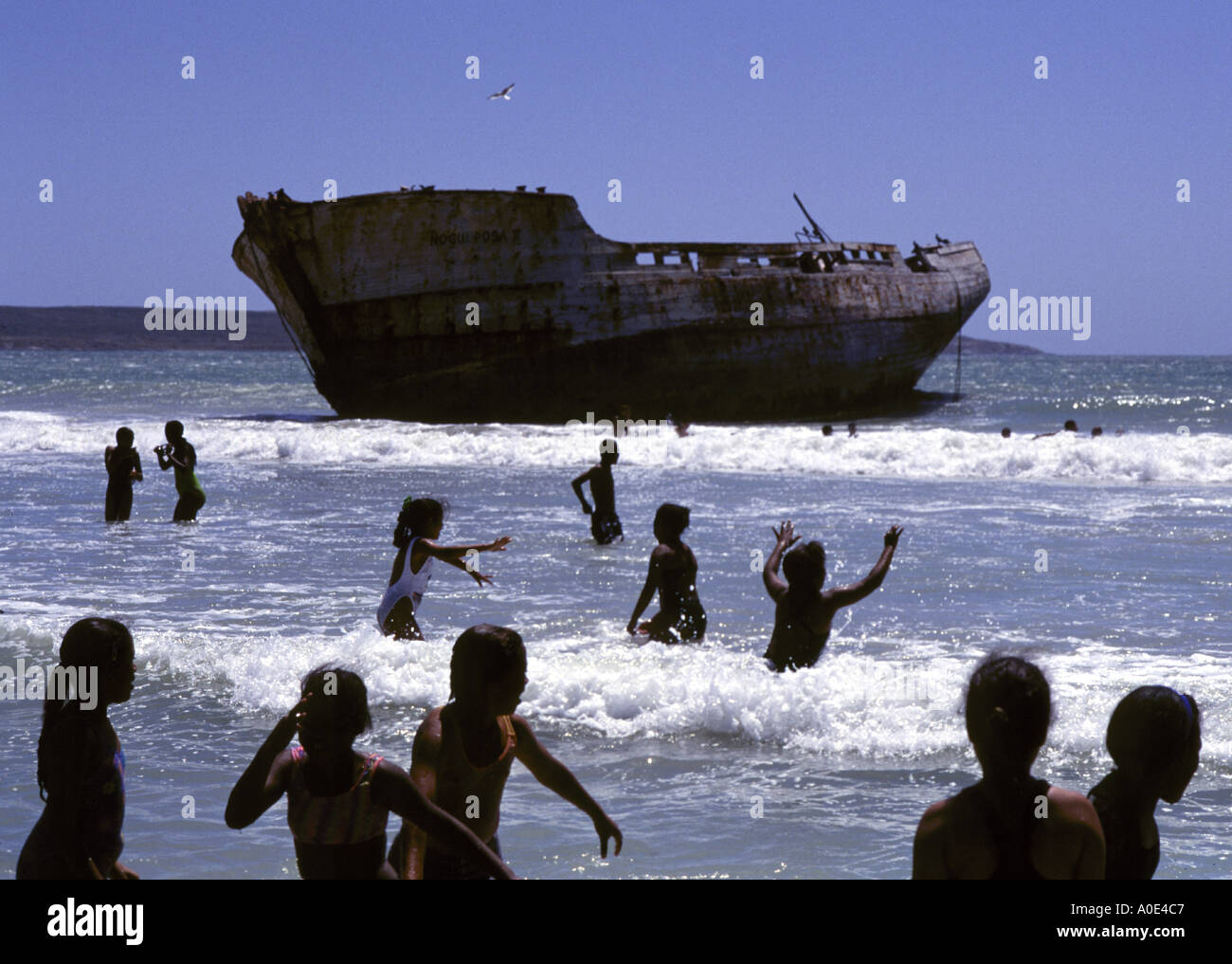 South African exotic location shipwreck South Africa People children playing in the ocean near a beached ship South Africa - Stock Image