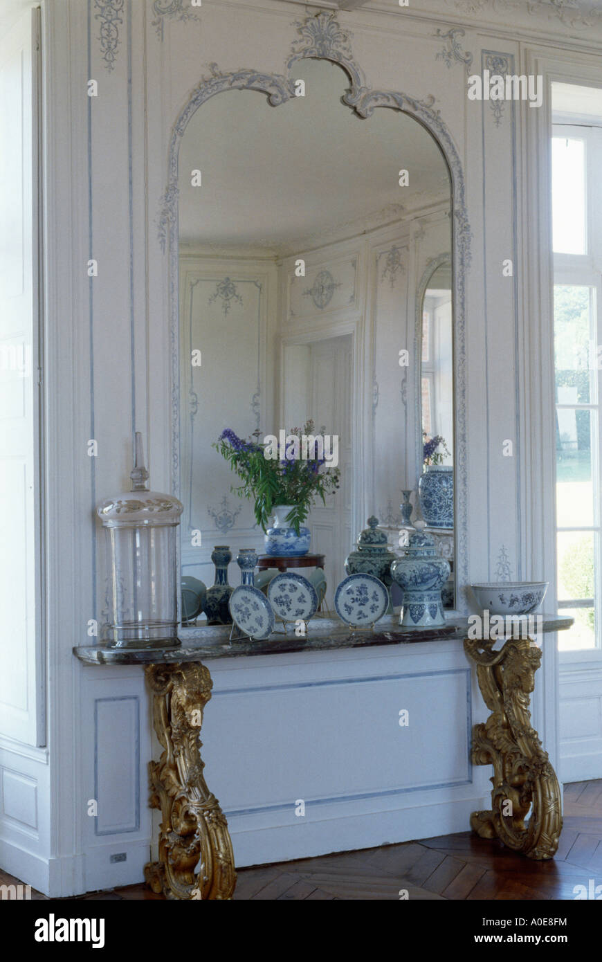 Large Mirror Above Antique Console Table In Traditional Hall In French  Townhouse