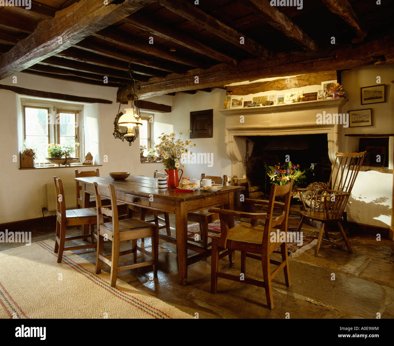 Chairs and table in front of fireplace in country diningroom - Stock Image