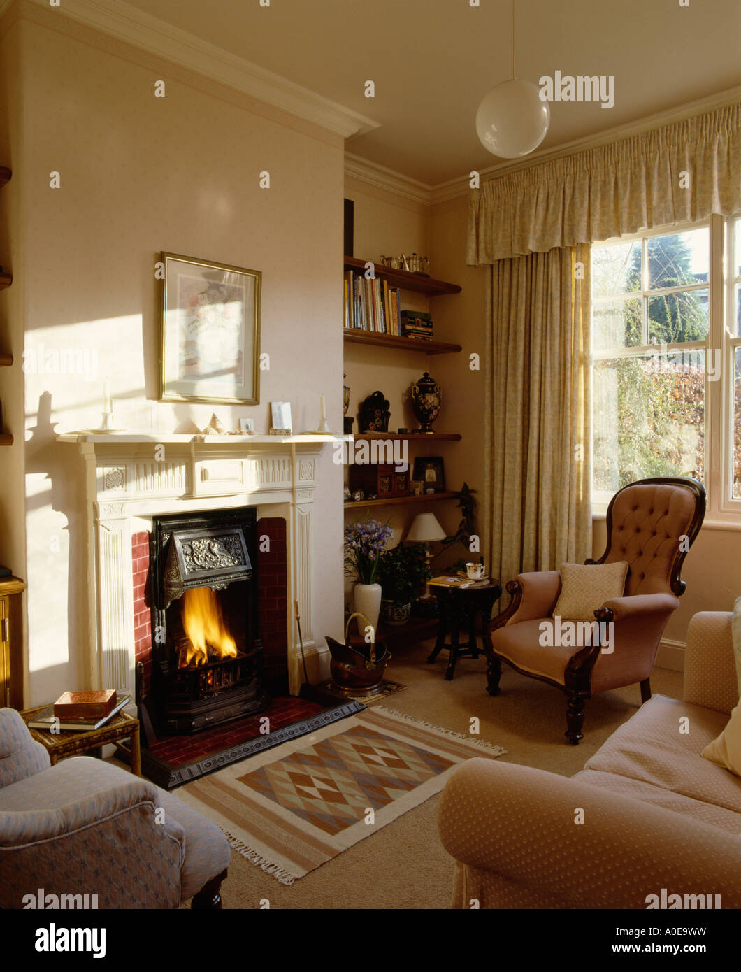 Fireplace With Fire Lit In Traditional Livingroom With