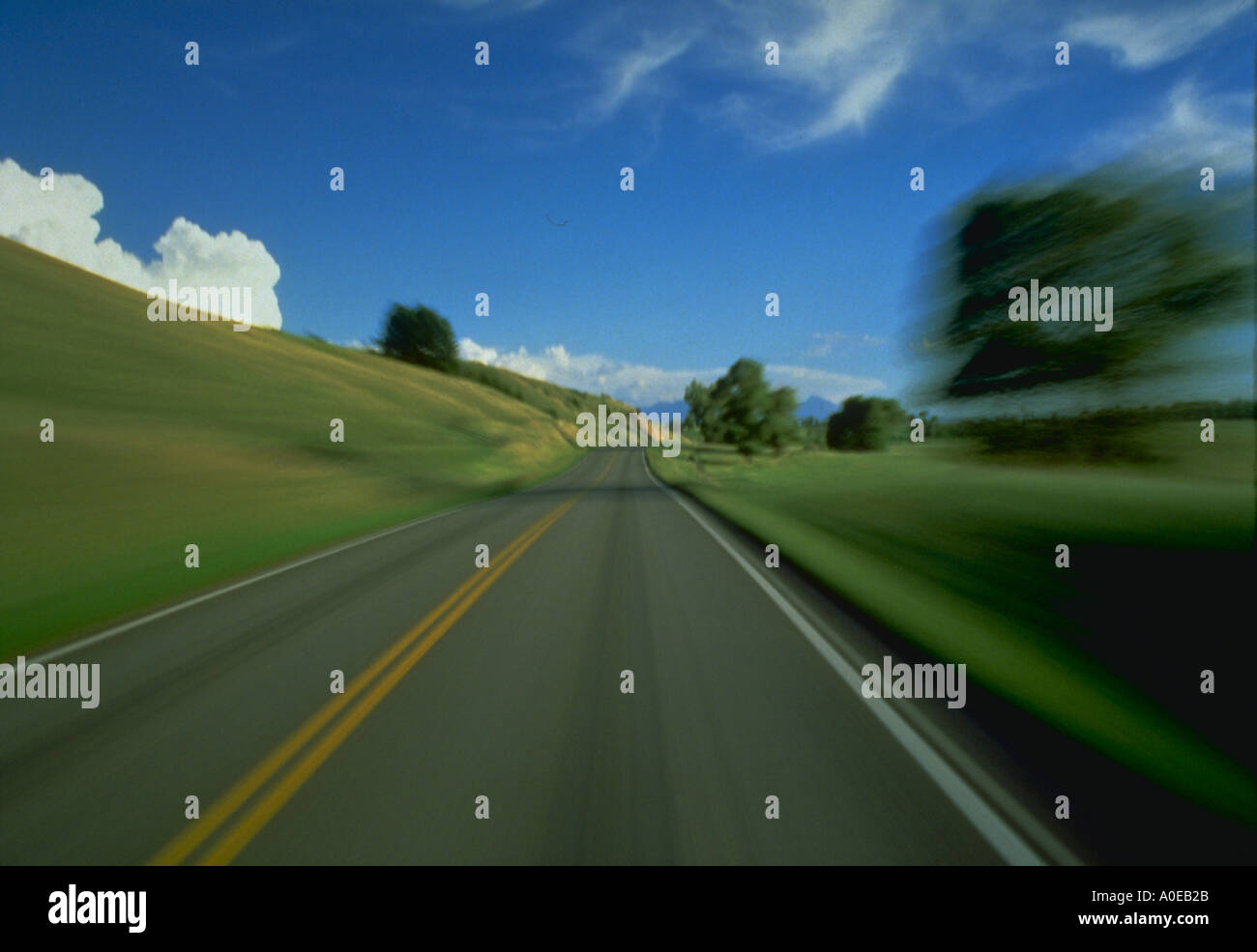 Road with blurred motion effect and blue sky and clouds Paradise Valley near Livingston Montana - Stock Image
