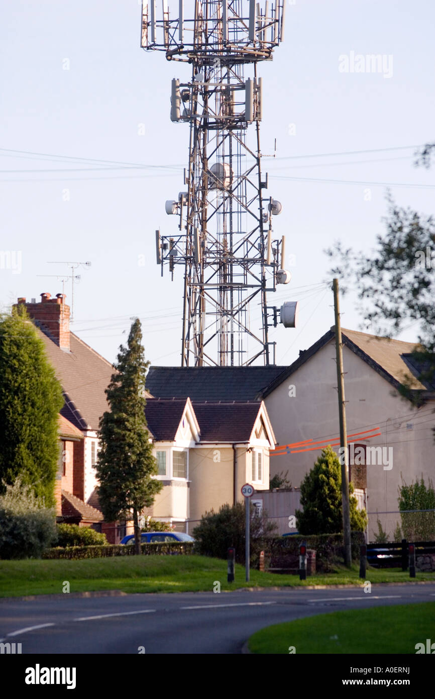 A mobile phone mast next to houses at Romsley Worcestershire UK - Stock Image