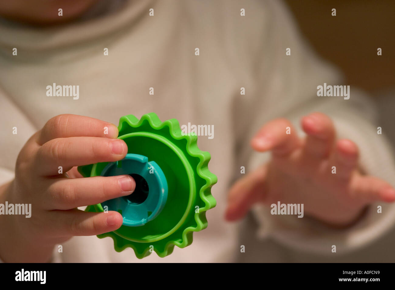 Young child plays with cog-shape toy - Stock Image