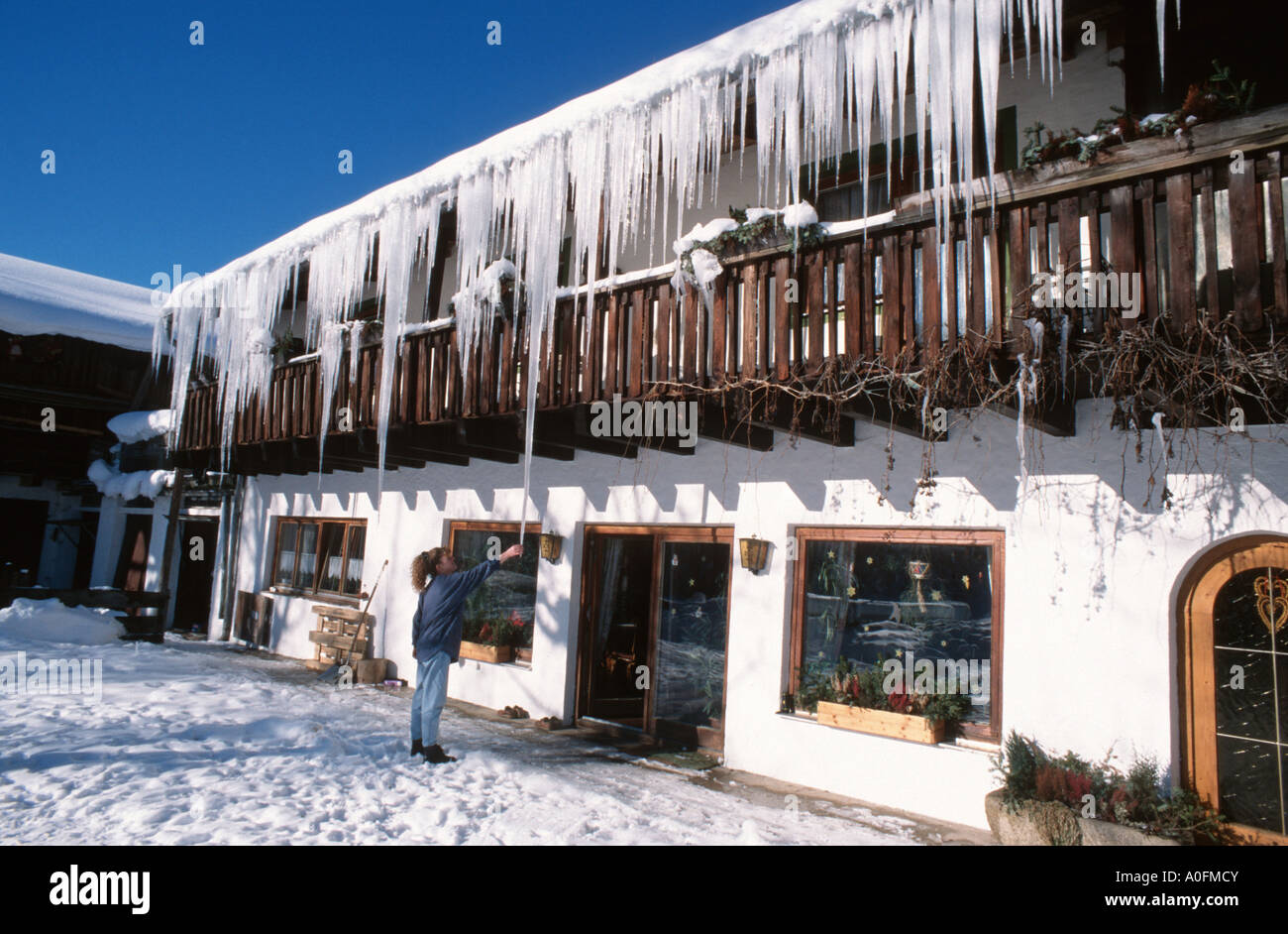 snow covered farmhouse, icicles hanging down the roof, Germany, Bavaria, Bavarian Forest - Stock Image