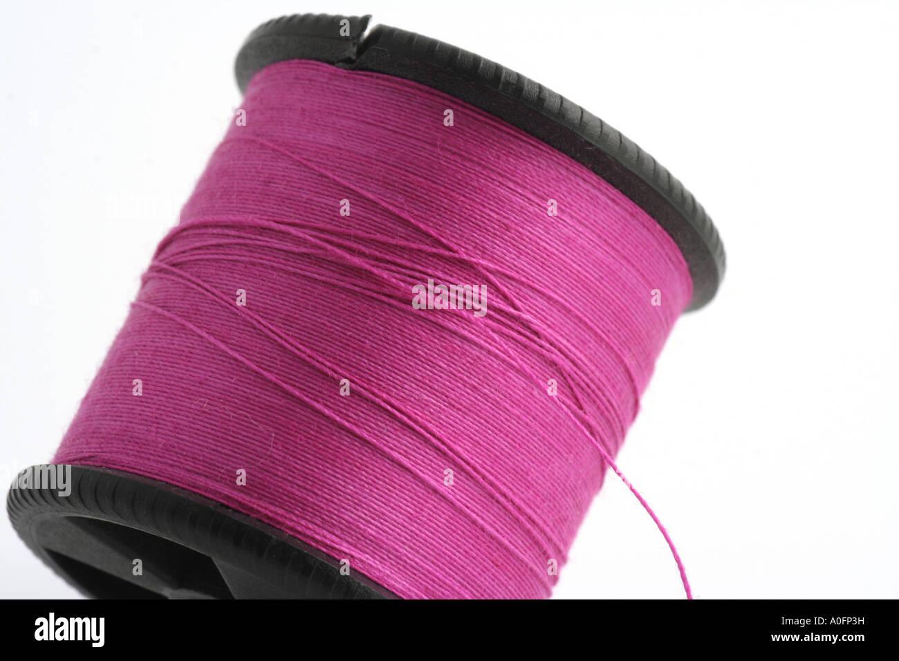 Bobbin of purple thread. - Stock Image