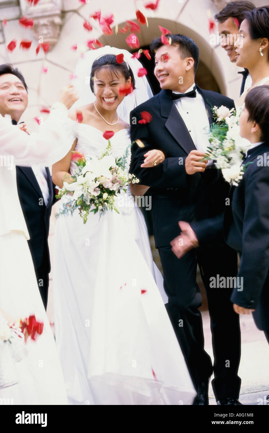 Flower petals thrown on a newlywed couple - Stock Image