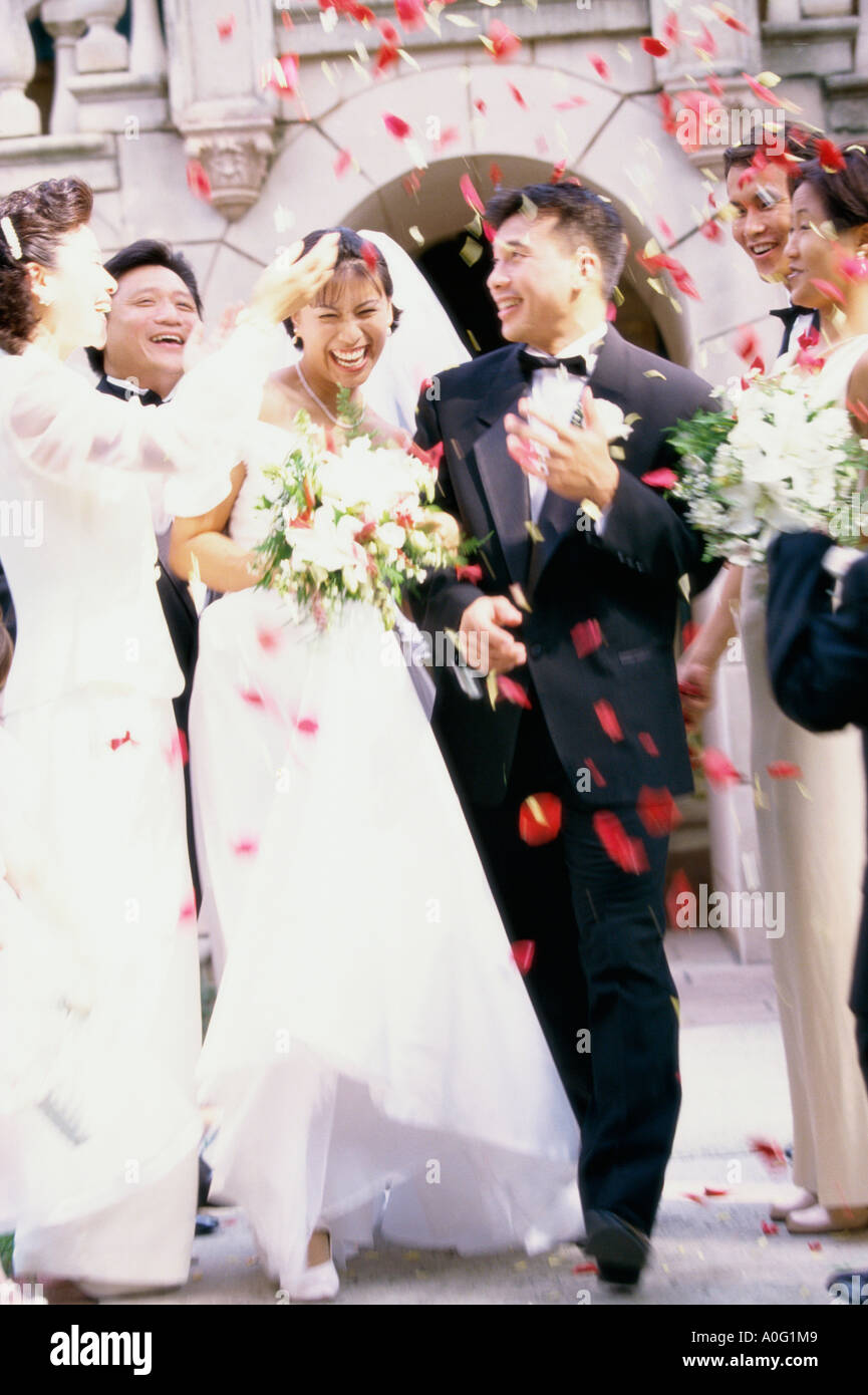 Flower petals being thrown on a bride and groom - Stock Image