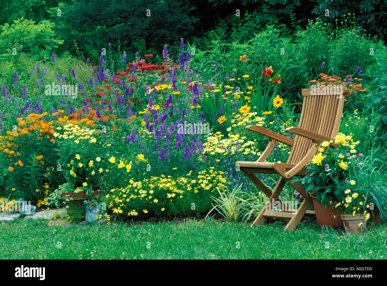 Wooden Chair In Colorful Flower Garden With Annuals And Perennials