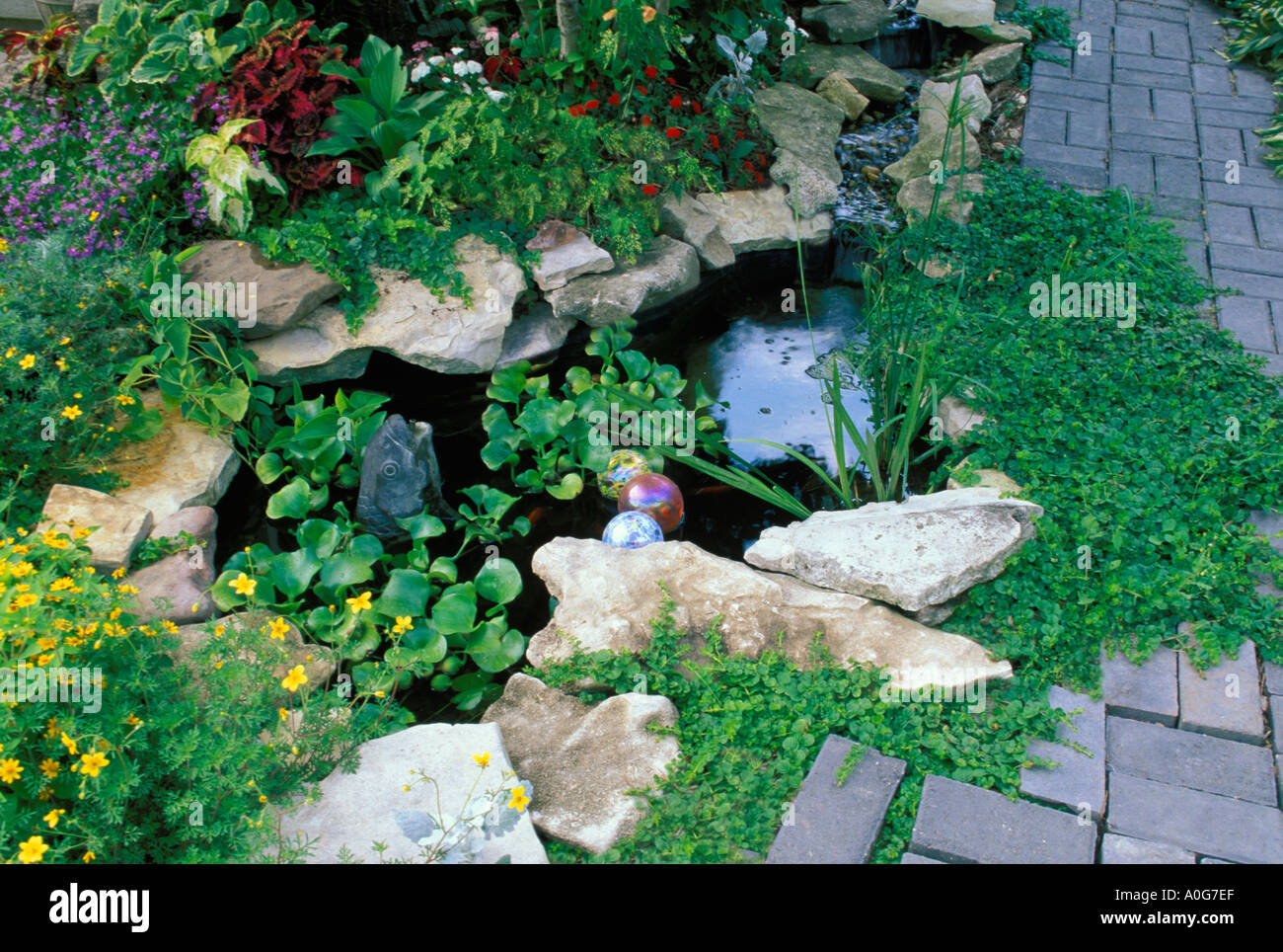 Small decorative fish pool with fountain waterfall in landscaped garden with brick paths and patio,  Midwest  USA Stock Photo