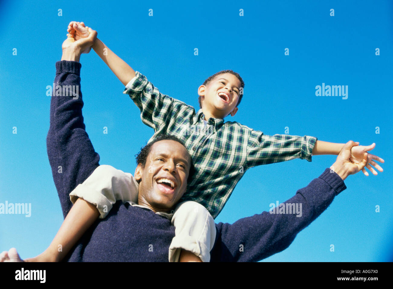 Low angle view of a father carrying his son on his shoulders - Stock Image