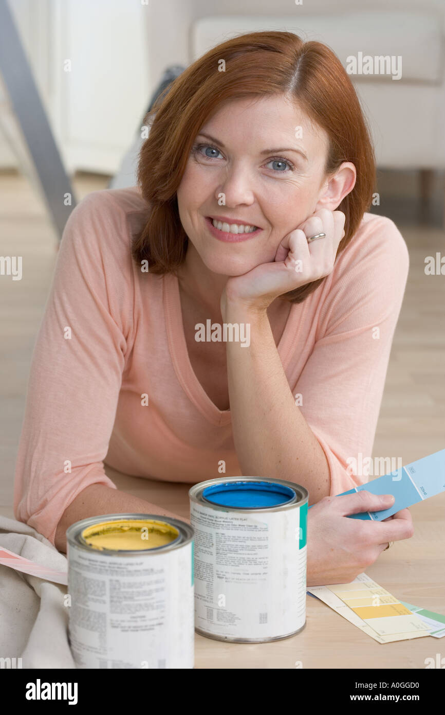 Smiling woman with paint samples - Stock Image