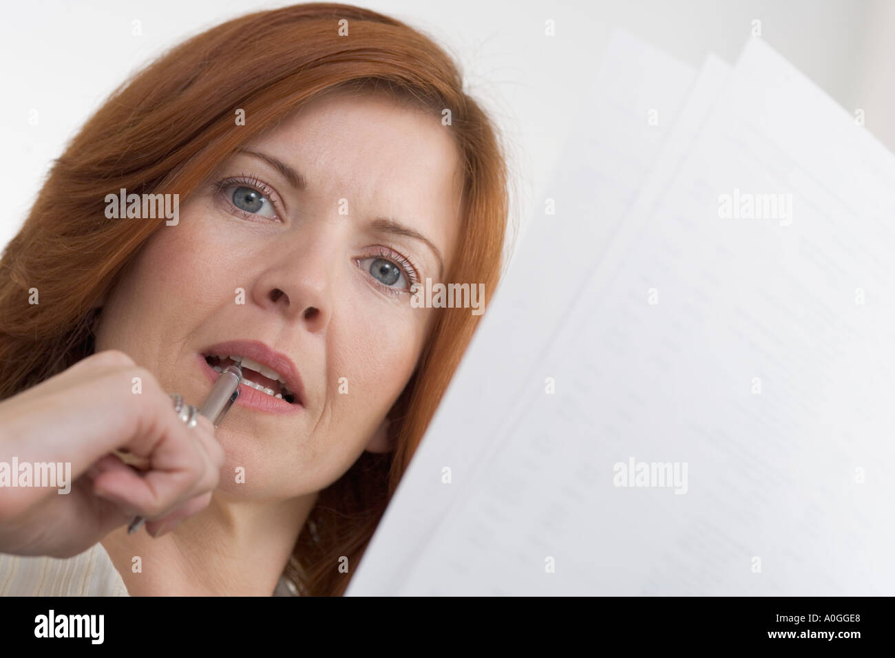 Woman thinking with papers and pen - Stock Image