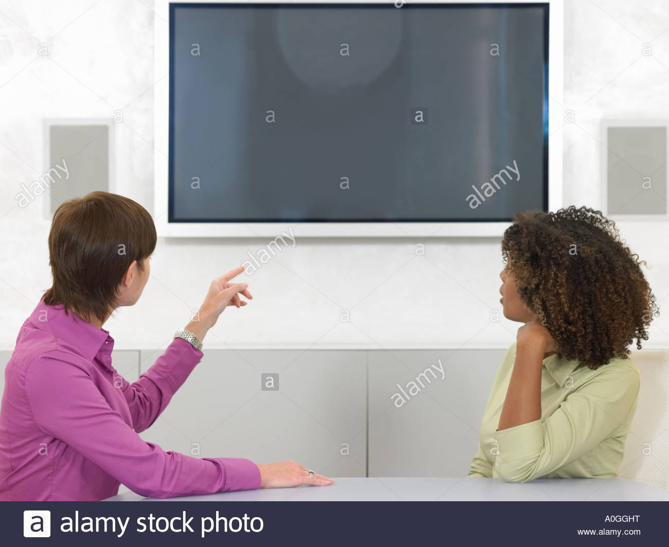 Colleagues looking at video screen - Stock Image