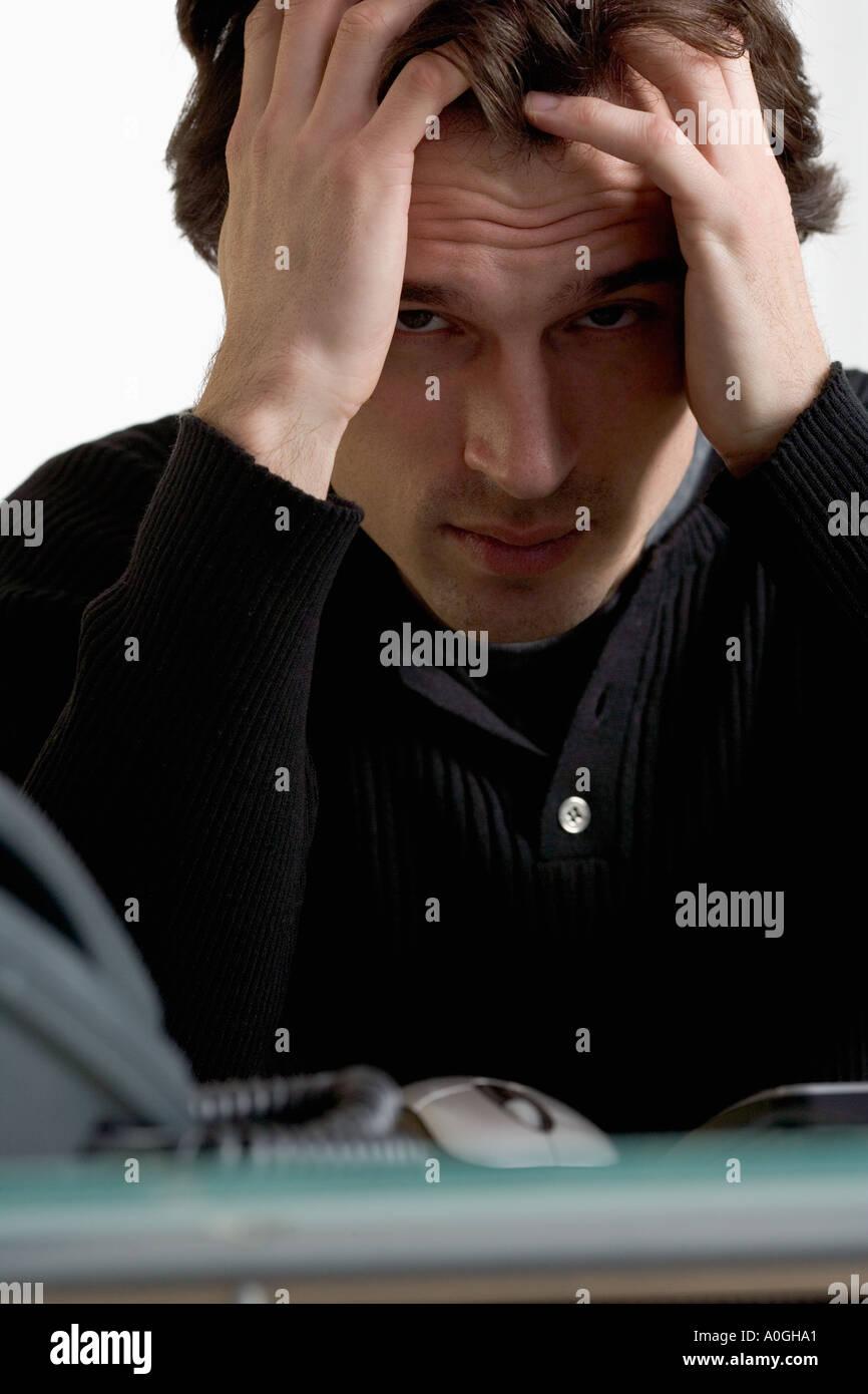 Closeup of upset man at desk - Stock Image