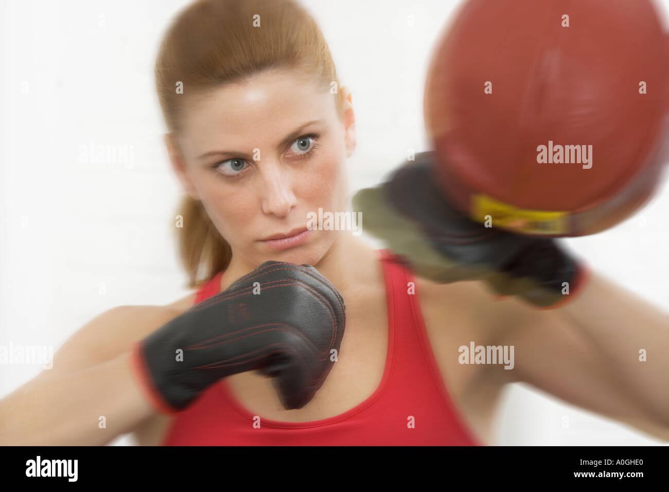 Female boxer hitting punching bag Stock Photo