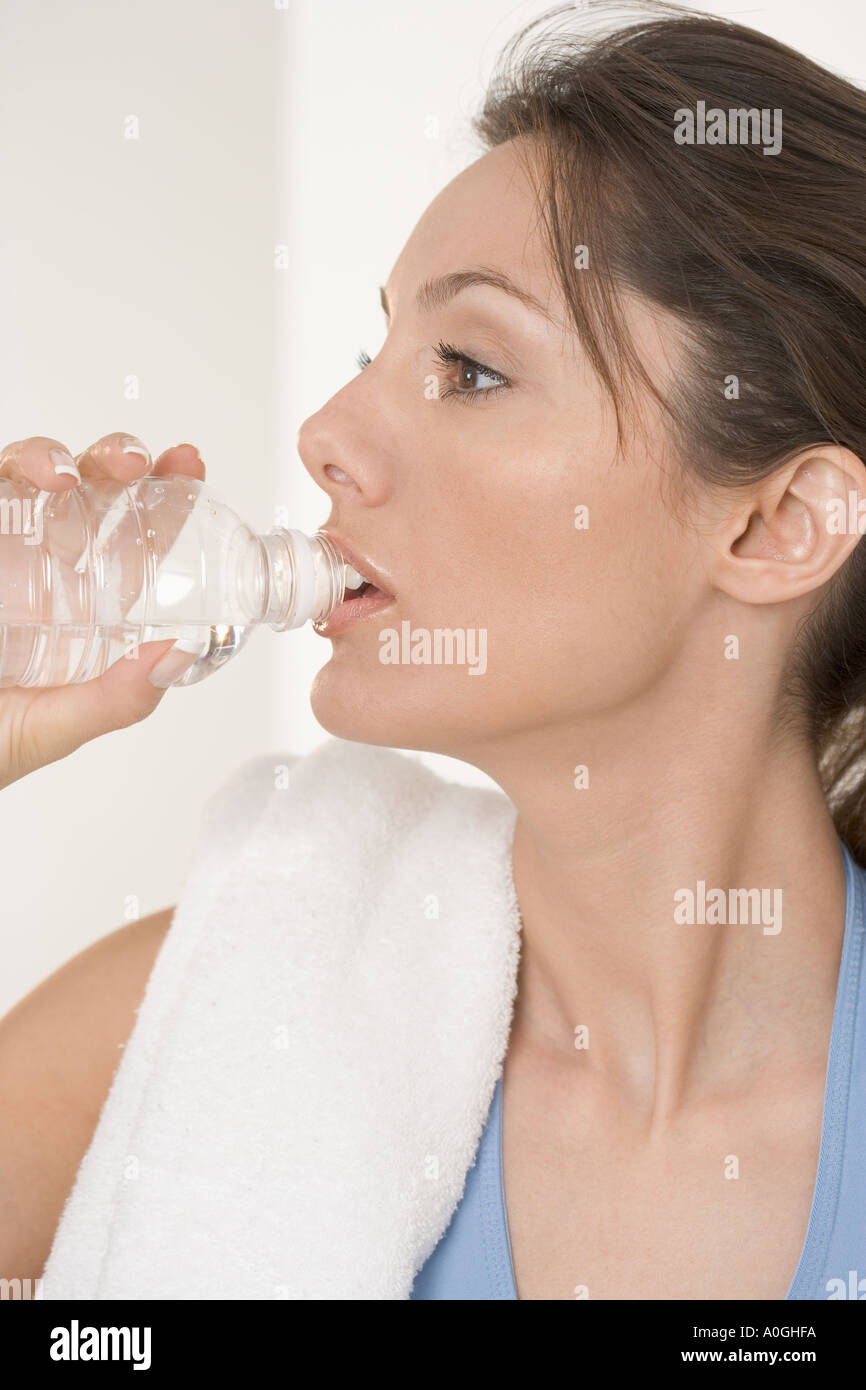 Woman drinking from water bottle - Stock Image