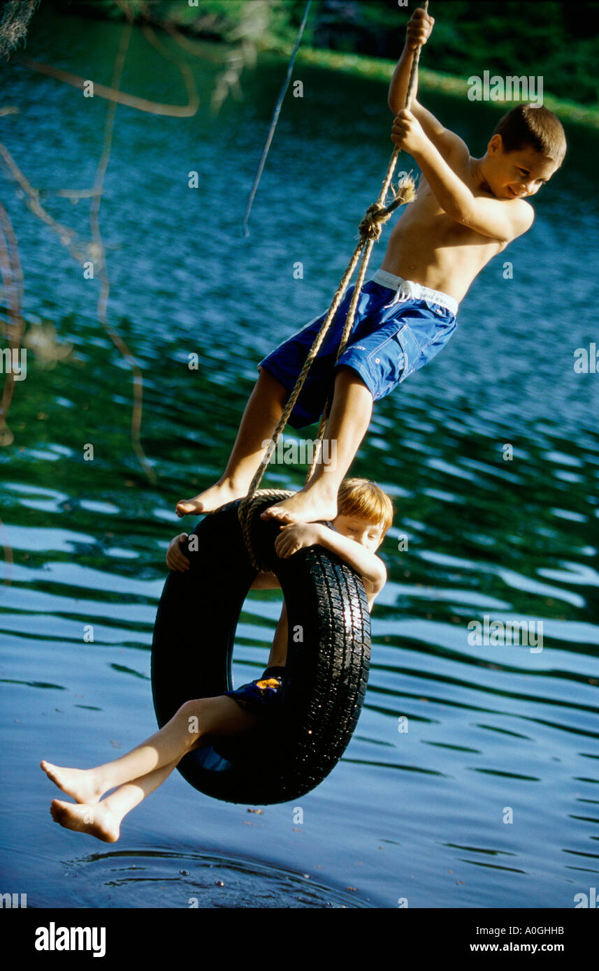 Two boys playing on a tire swing Stock Photo