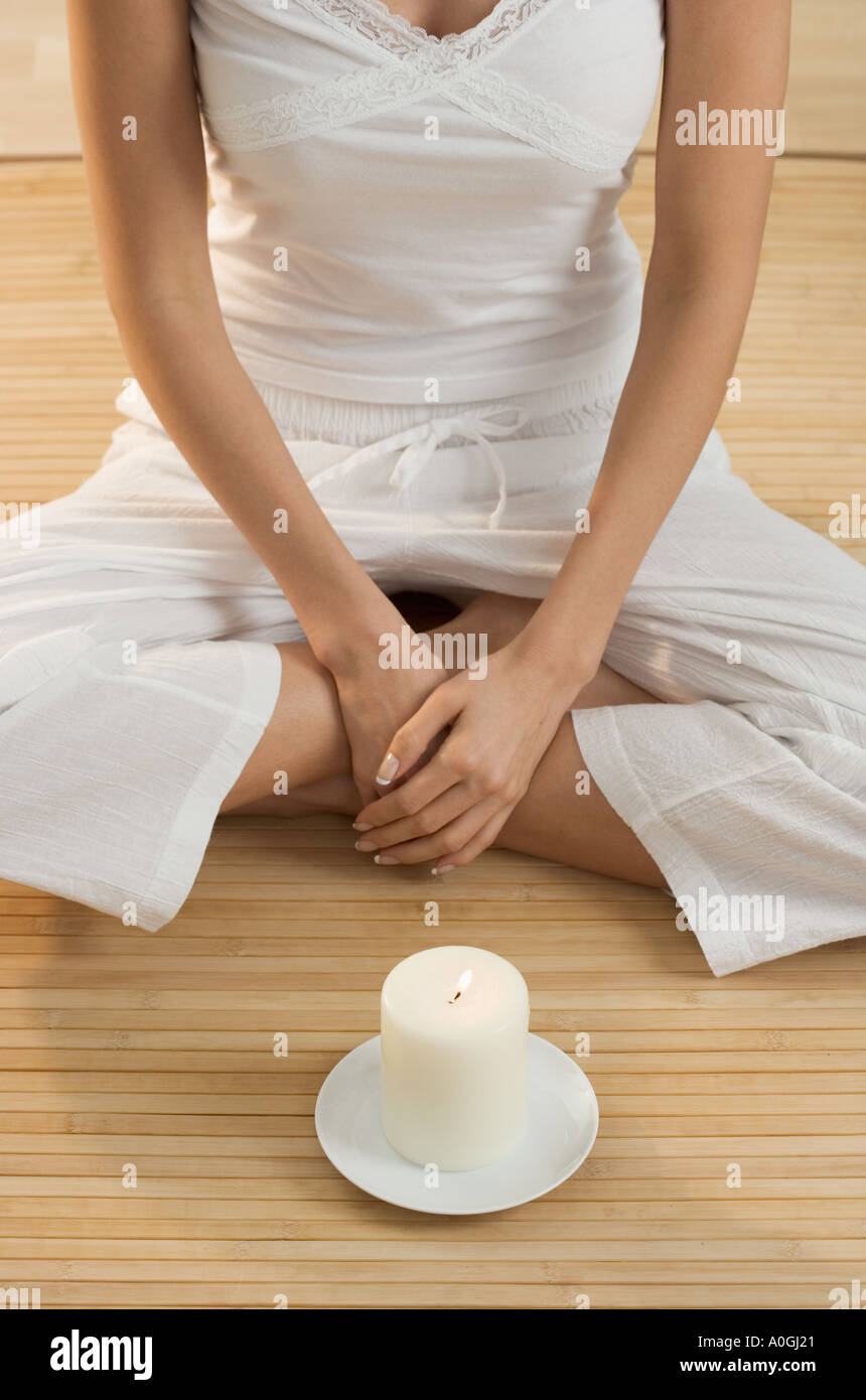 Cross legged woman s torso with candle - Stock Image