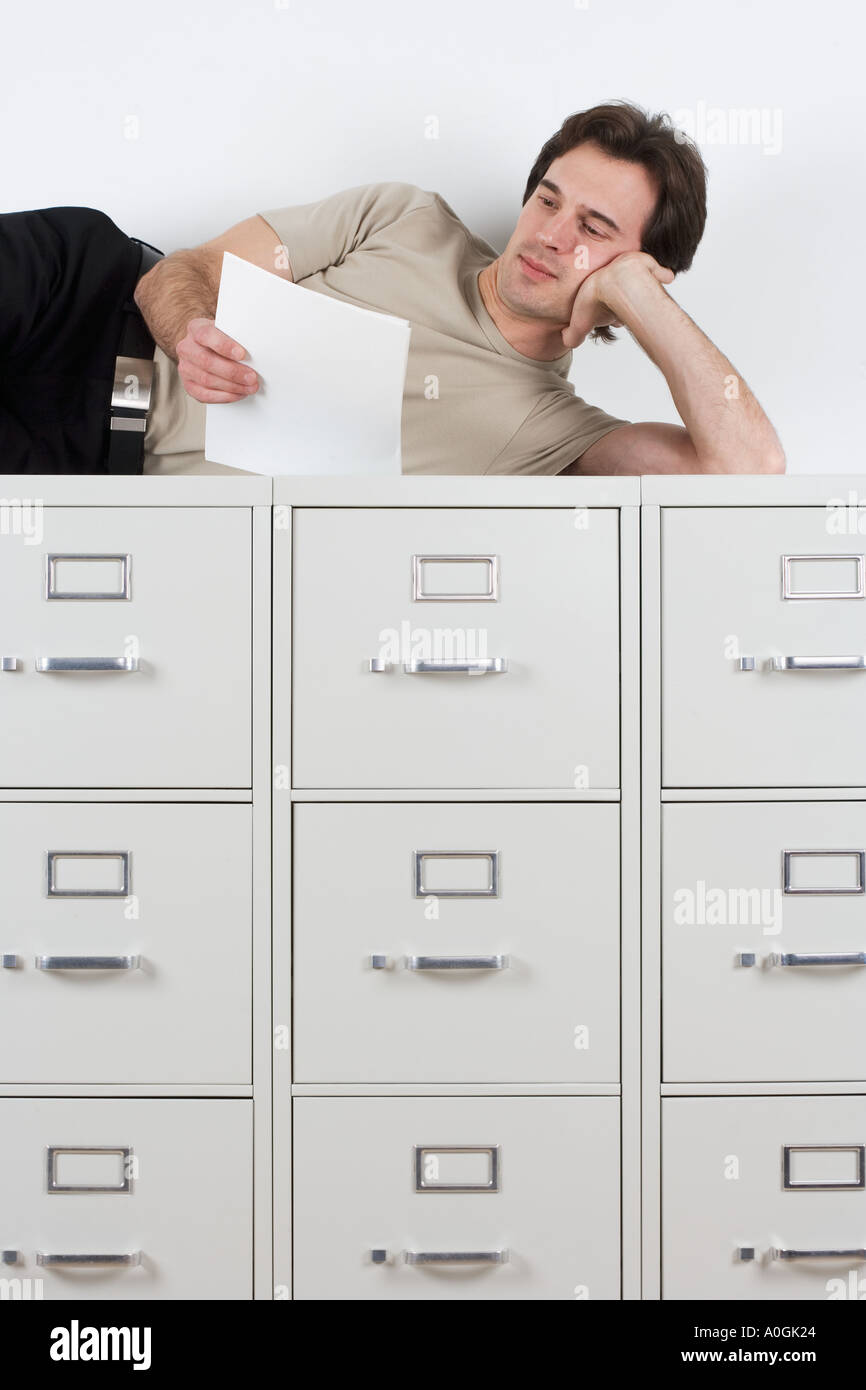 Man reading lying atop file cabinets Stock Photo