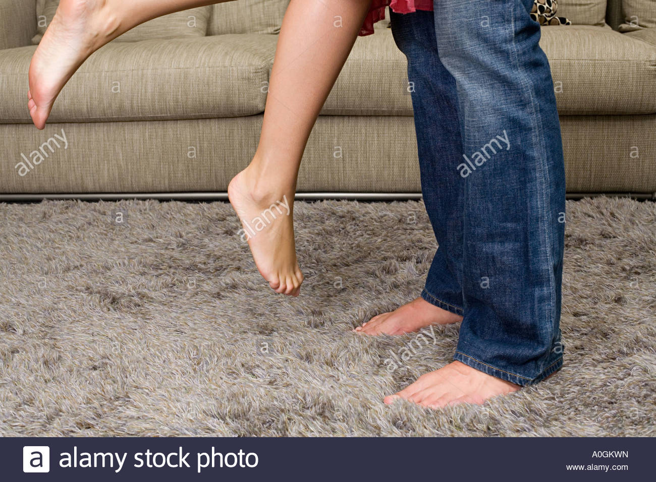 Young couples legs in living room - Stock Image