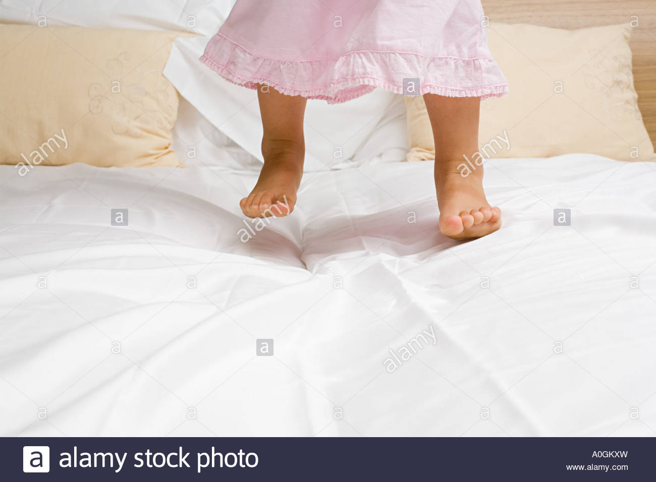 Girl jumping on a bed - Stock Image