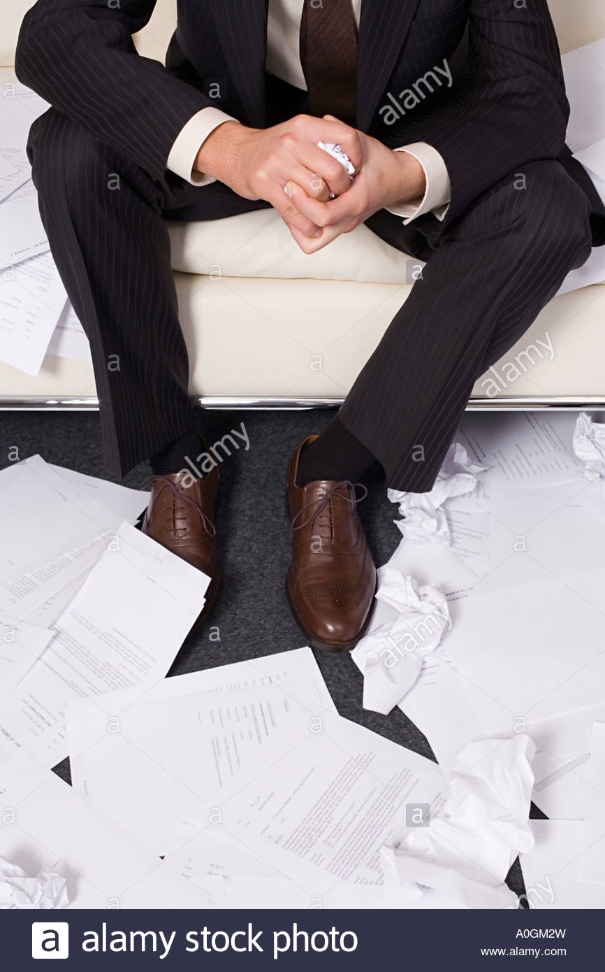 Businessman surrounded by crumpled paper - Stock Image