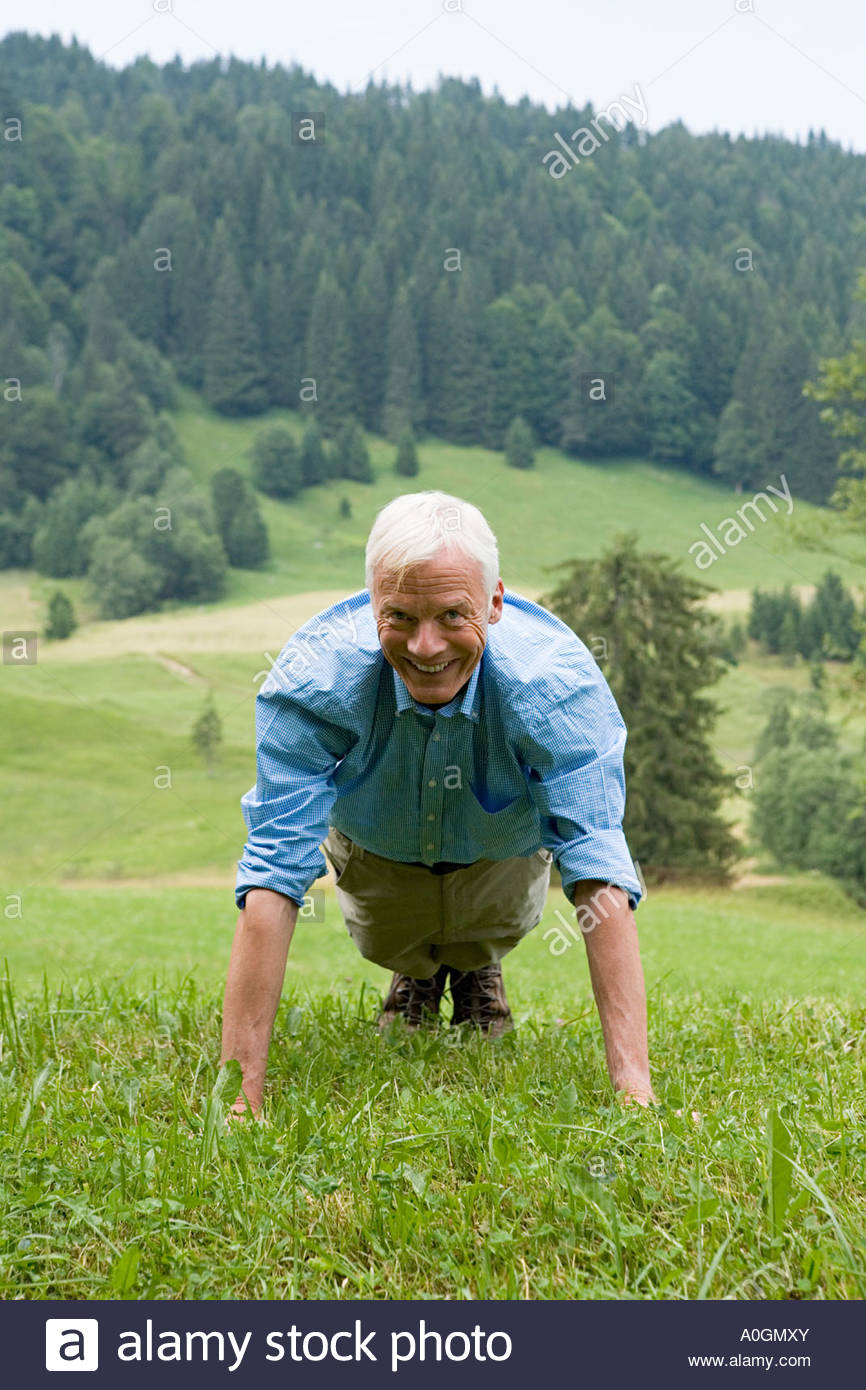 Man doing press ups in a field - Stock Image