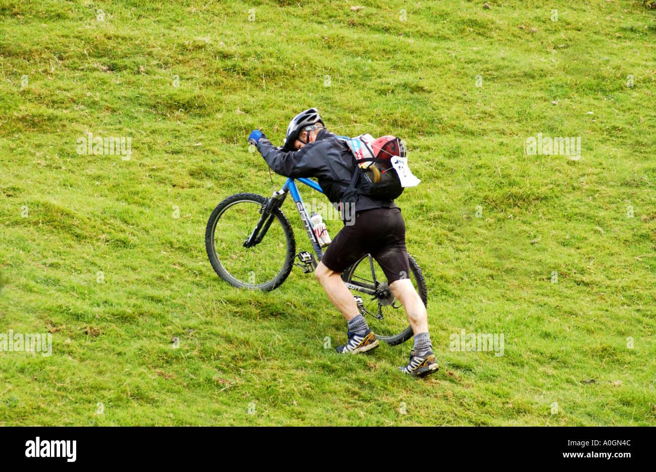 Man pushing mountain bike up steep grassy hill Stock Photo ...