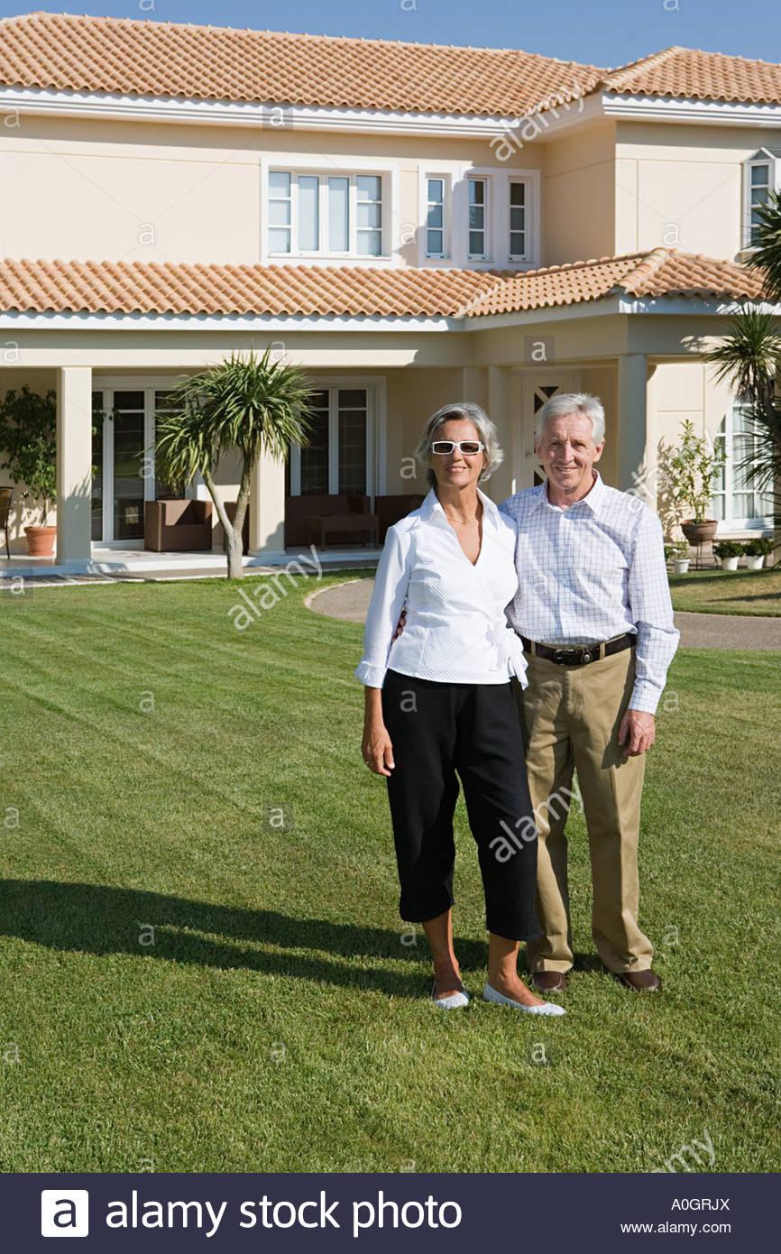 Couple stood outside of villa - Stock Image