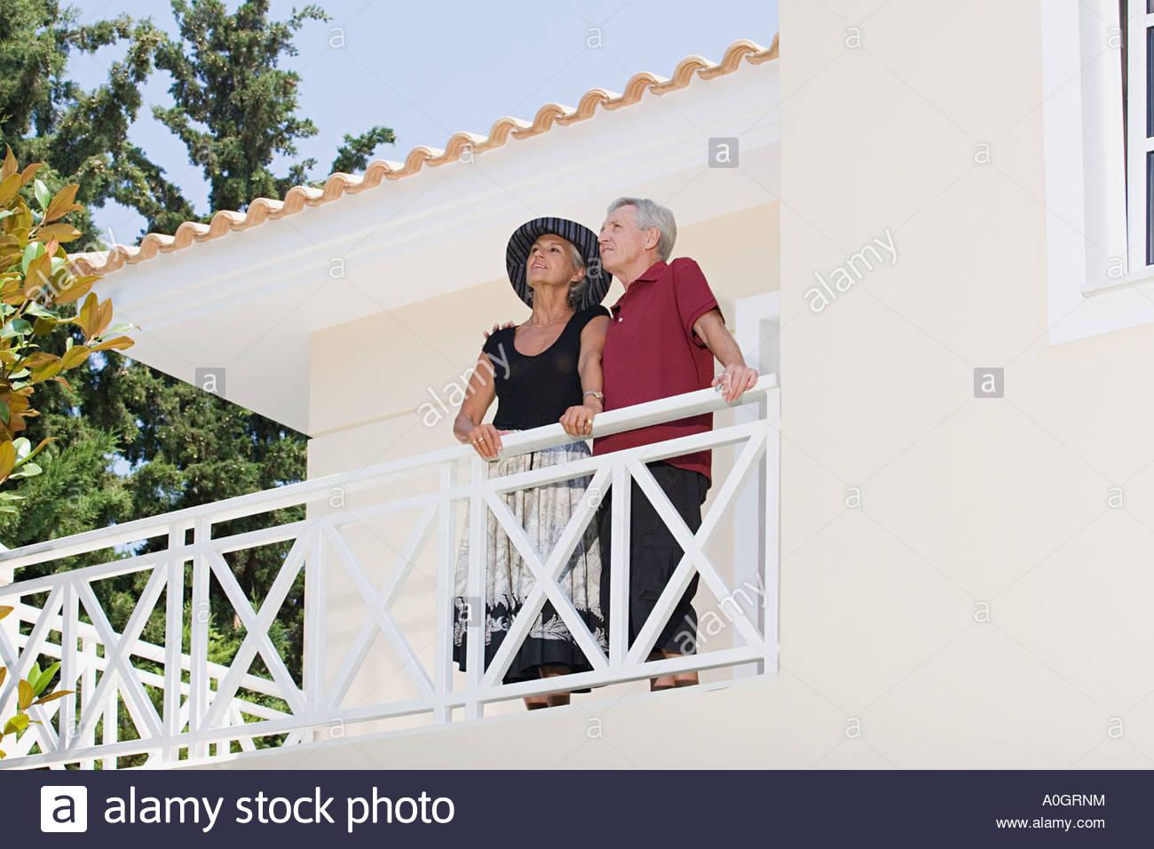 Couple stood on balcony - Stock Image