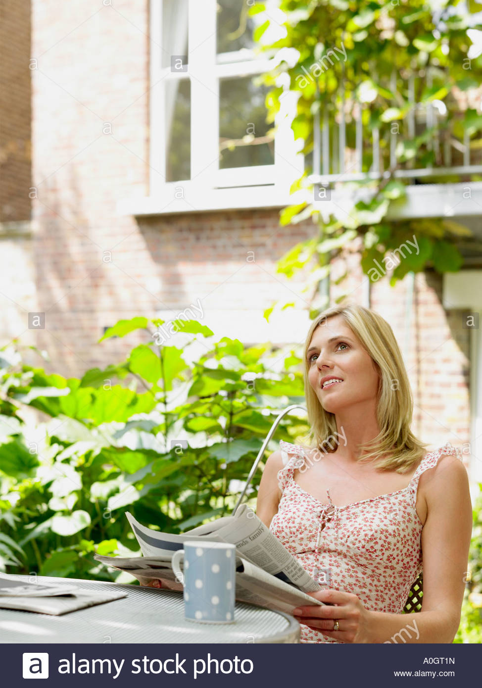 Woman in garden with newspaper - Stock Image