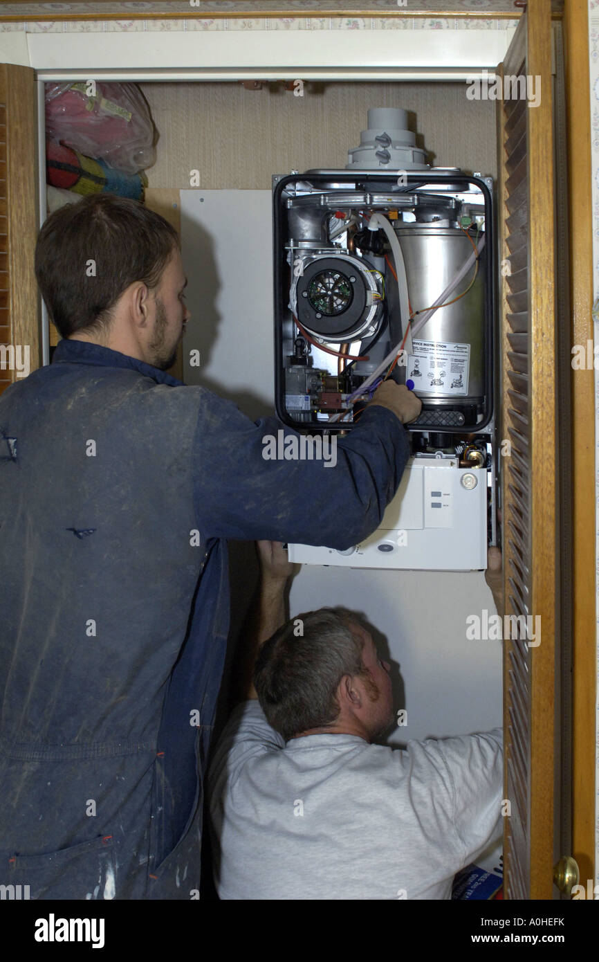 Two adult male workers installing a new Combi boiler into a house ...