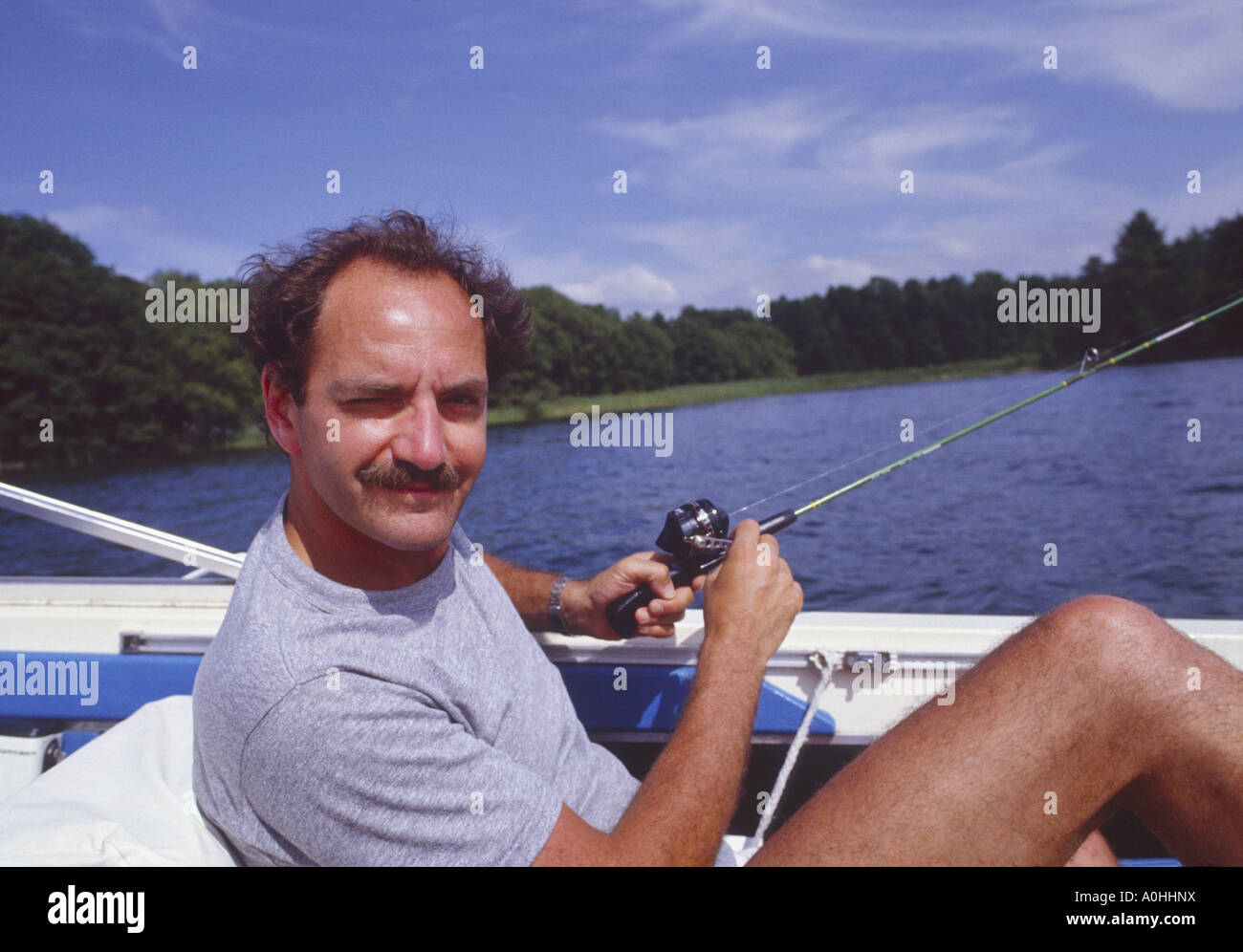 man fishing in boat using inexpensive rod and reel - Stock Image