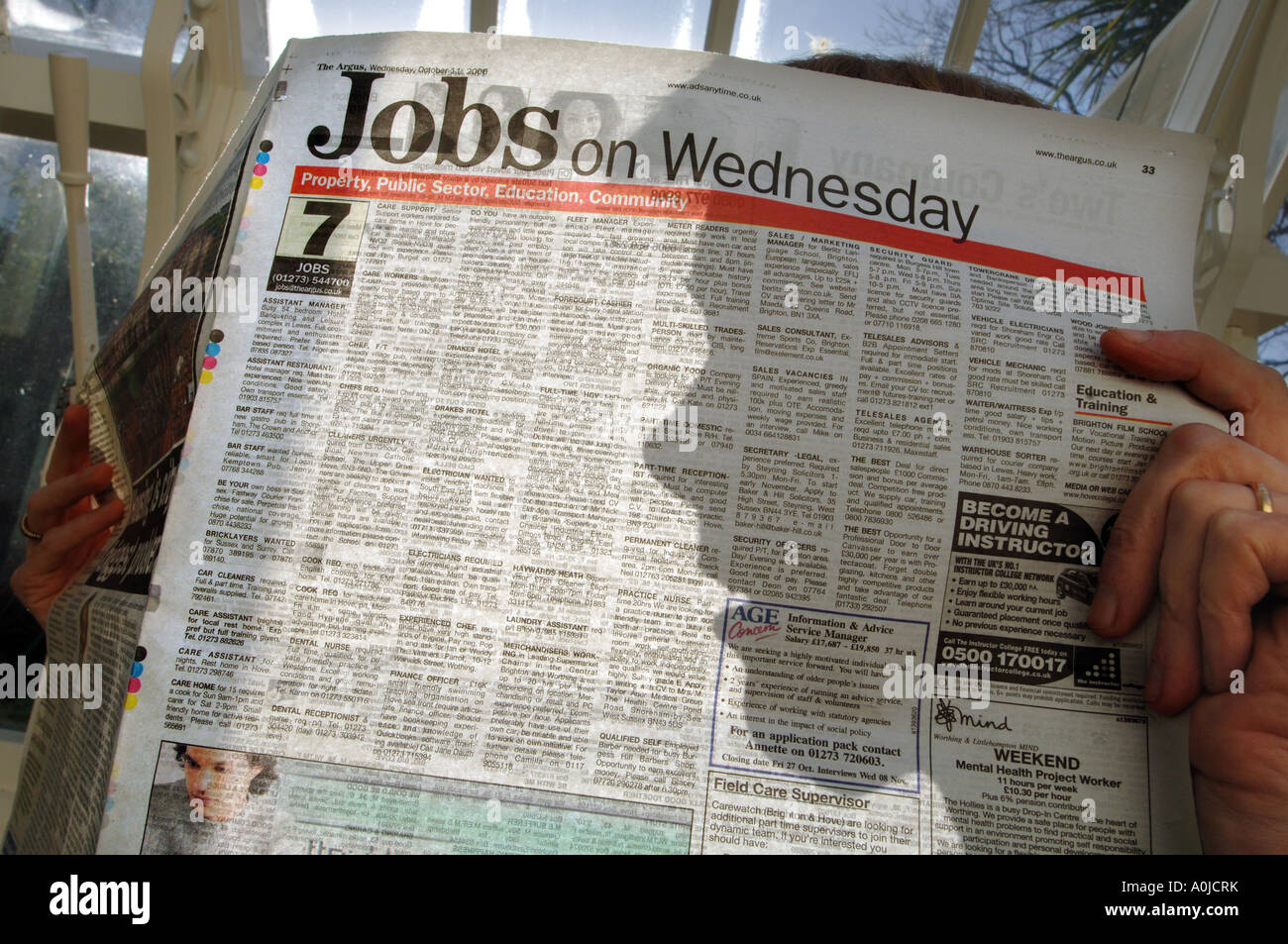 Silhouette of someone looking at job ads in a paper - Stock Image