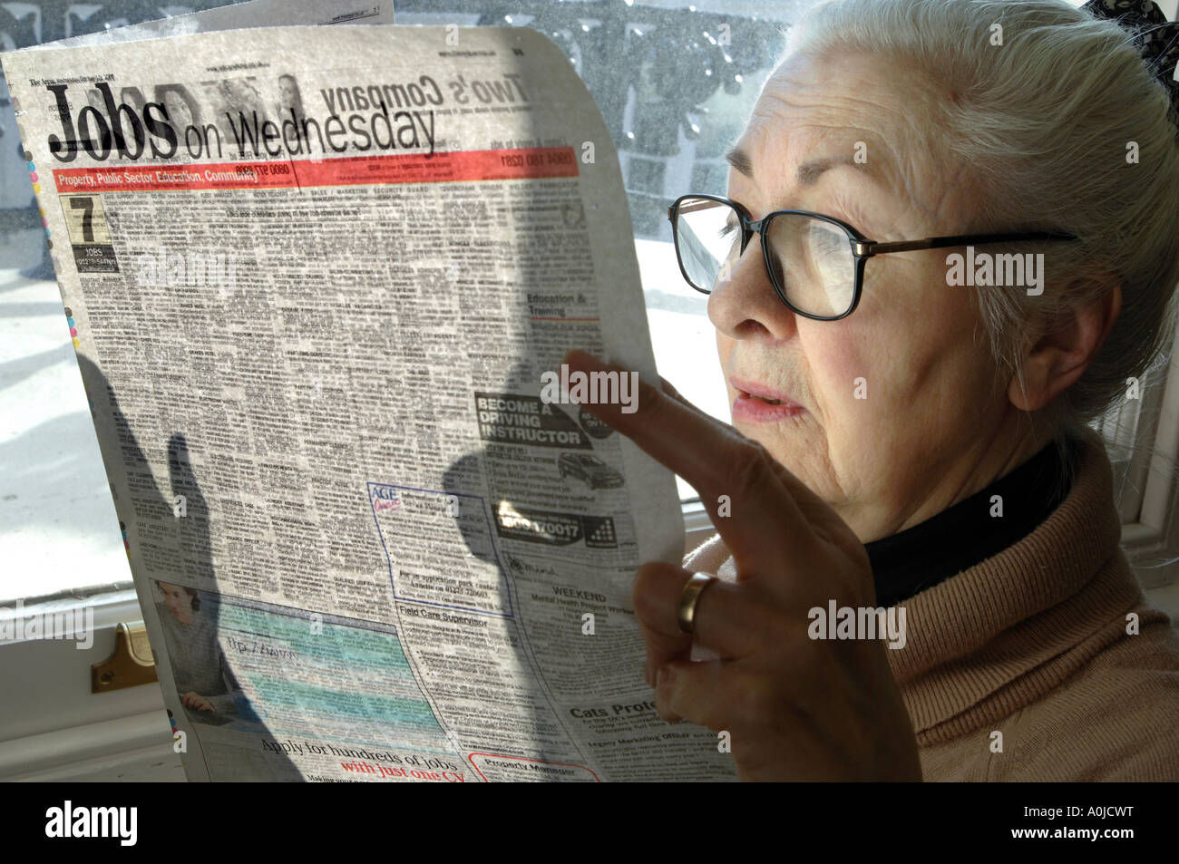 A thoughtful looking woman pensioner surveys the jobs on offer in her local paper. - Stock Image