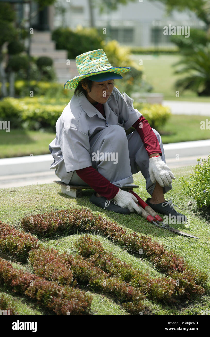 A lady gardener trims the lawn with a set of shears in Dusit Park Bangkok Thailand - Stock Image