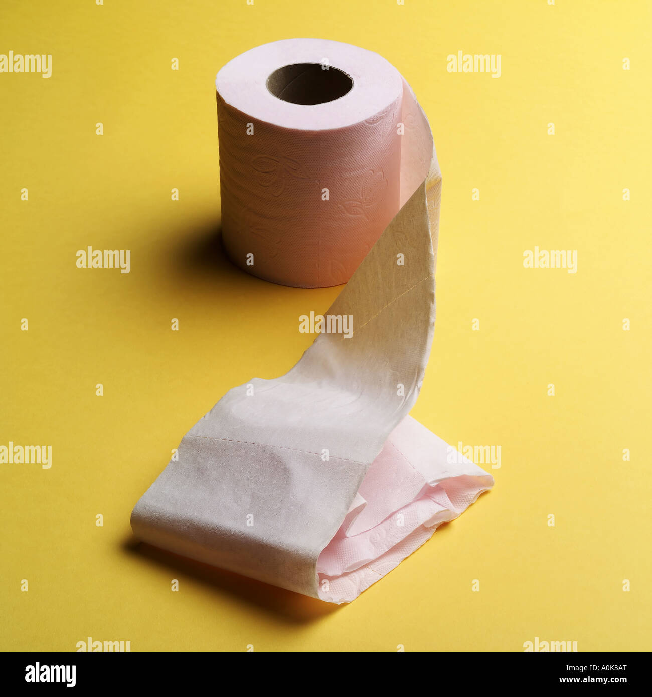 ROLL OF PINK TOILET PAPER ON YELLOW BACKGROUND - Stock Image