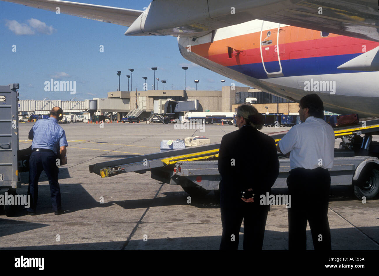United Air Lines supervisors watch baggage handler unload jet at Detroit airport - Stock Image