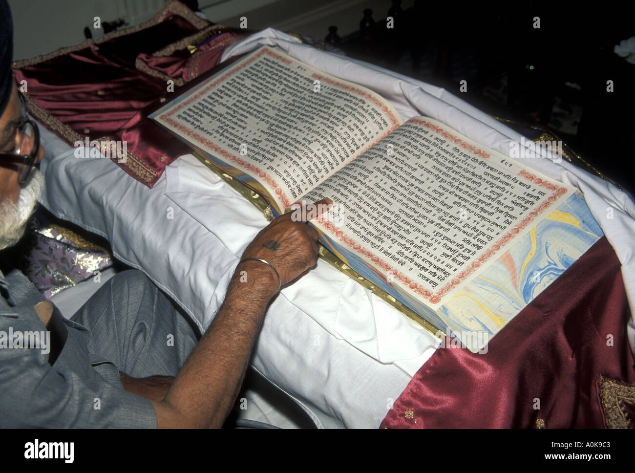 The Granthi  choosing a new baby's name from the Guru Granth Sahib or sacred Sikh texts - Stock Image