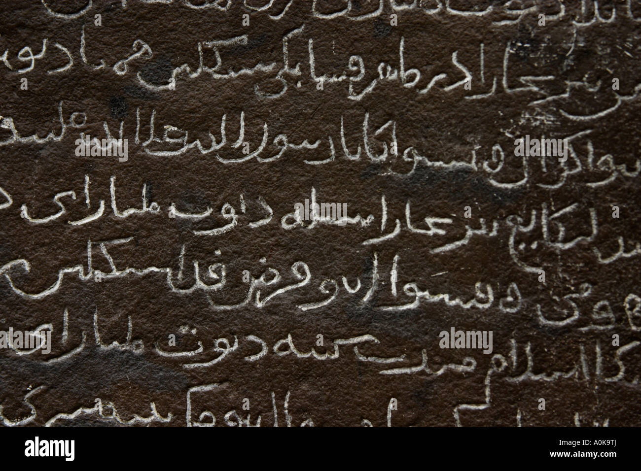 jawi or arabic letters written on stone - Stock Image