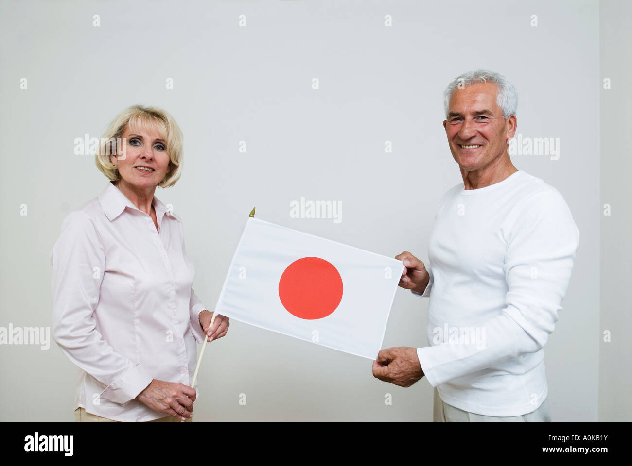 two mature caucasian people holding Japanese flag - Stock Image