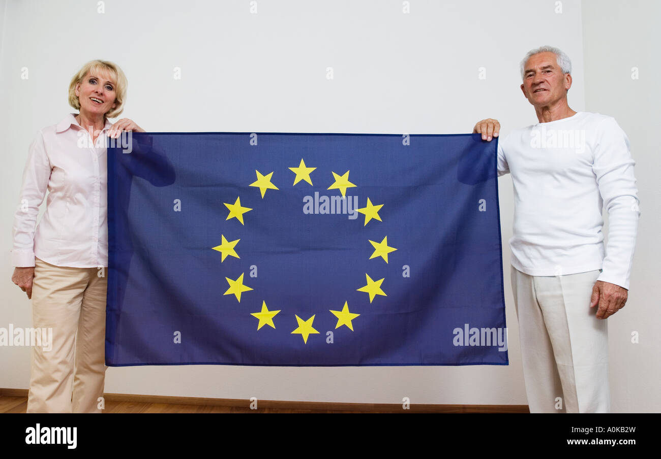 mature couple holding European Union flag - Stock Image