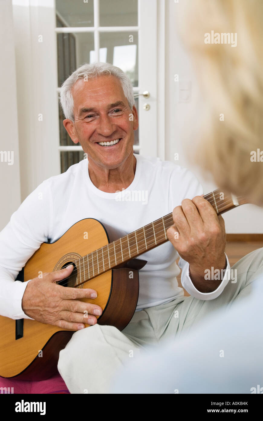 smiling mature man looking tenderly at his wife while playing guitar - Stock Image