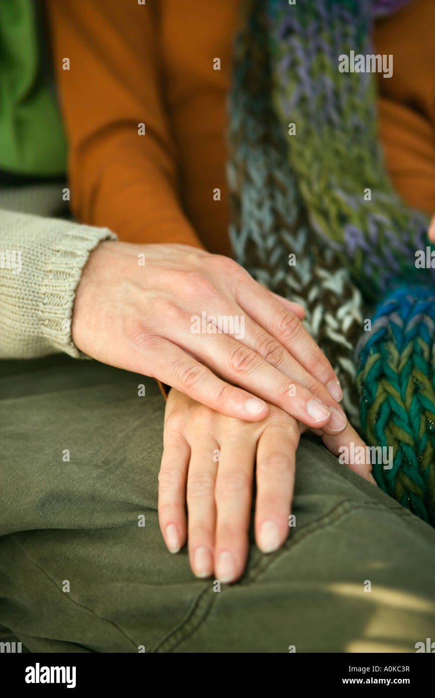detail of woman and man tenderly holding hands - Stock Image