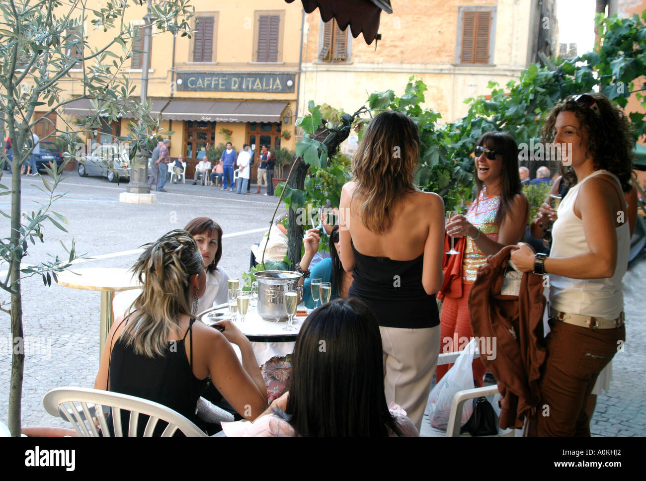 Girls in the town of Cagli in Le Marche, Italy, meet for an evening drink and chat at the bar in the piazza Stock Photo