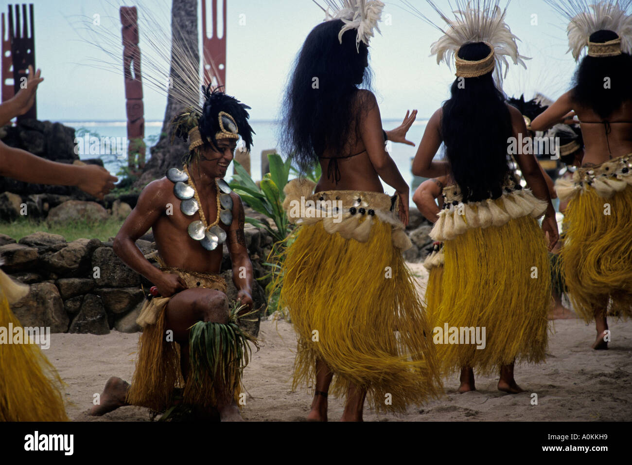 Tahitian men and women in traditional costumes perform Polynesian dances - Stock Image