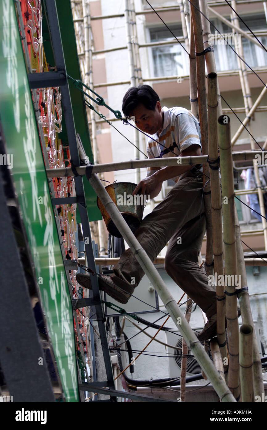 Worker paints a restaurant sign in Wanchai, Hong Kong - Stock Image