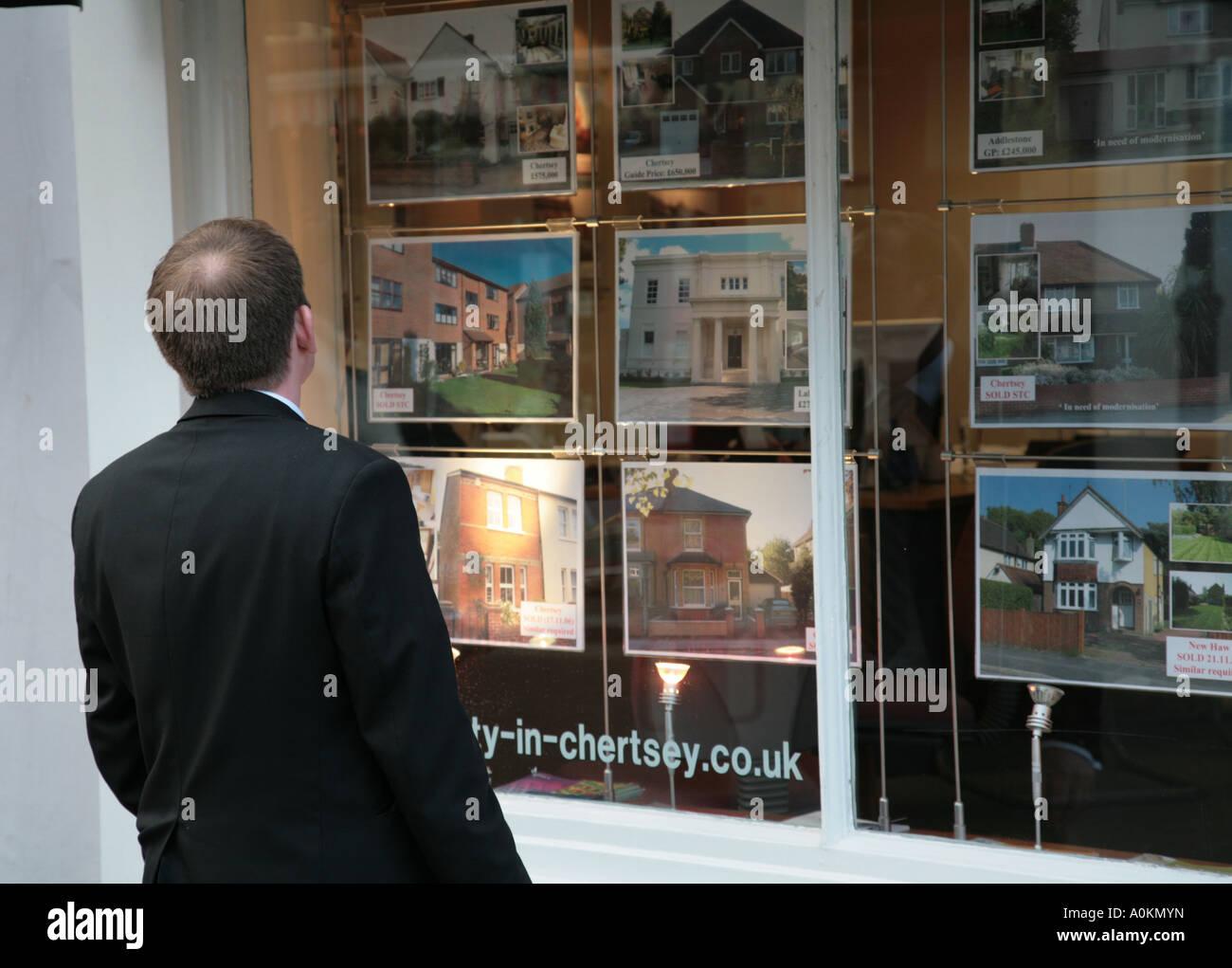 man browsing estate agent window - Stock Image